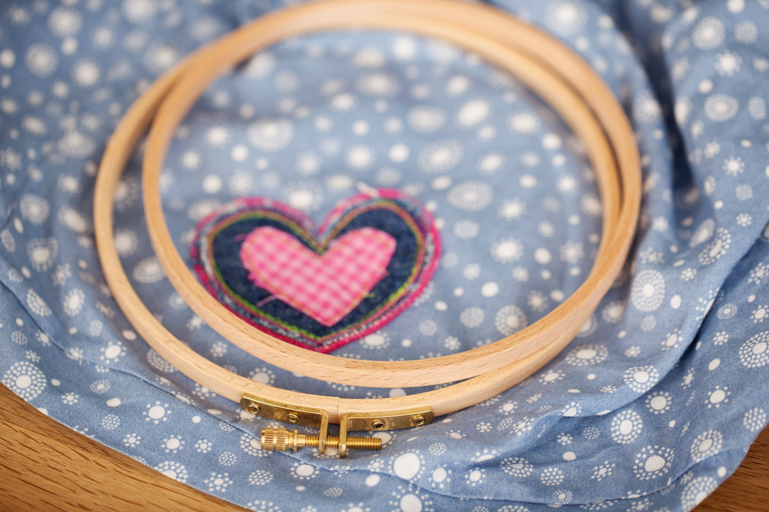 21230775 - closeup of embroidery hoops with heart on fabric in workshop